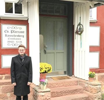 Foto: Pfarrer Noll vor dem Pfarrhaus, das nun mit Nahwärme versorgt wird.